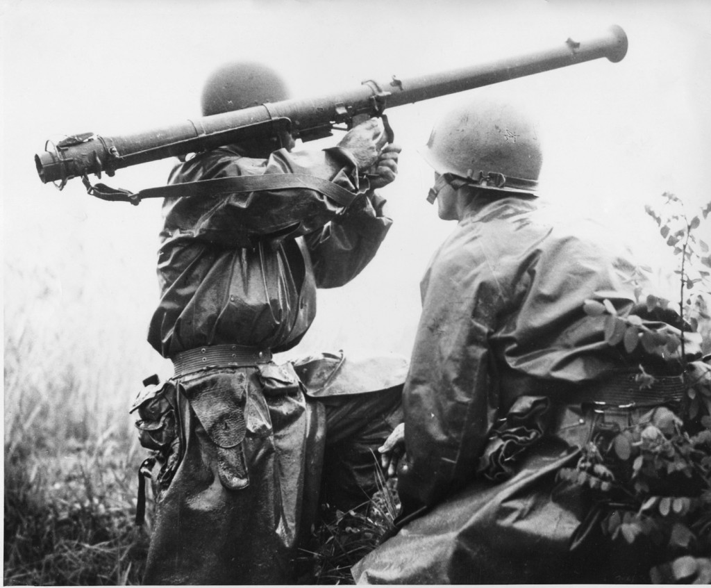 "A team mans a Bazooka at the Battle of Osan. Members of the 24th Infantry Division, first United States ground units to reach the front, go into action against North Korean forces at the village of Sojong-Ni, near Osan. At right is Private First Class Kenneth Shadrick, who was killed by enemy fire a few moments after this photo was made, thus becoming the first United States soldier to die in the Korean campaign."" Photo by Charles Turnbull. Image from Wikimedia Commons."