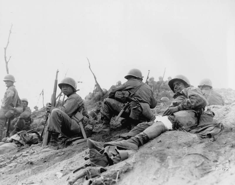 "Cpl. Sam Ayala of Niles, Calif., Co. L, 7th RCT, U.S. 3rd Infantry Division, waits for medical evacuation from Hill 717, Cpl. Ayala was wounded while engaged in a bitter grenade battle with deeply entrenched Chinese Communism. 3 July 1951. Korea. Photo from U.S. Army Signal Corps archive. Photo #8A/FEC-51-23541 (Brigham)."" Image from U.S. Army."