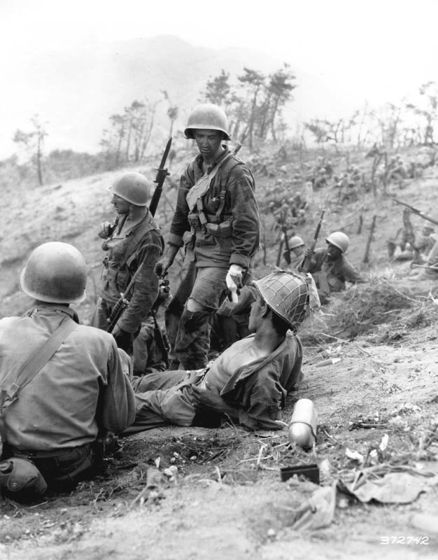 "Hit in the back during a grenade duel, Corporal Dominick F. Zegarelli, (Utica, N.Y.) Company L, 7th Regimental Combat Team, U.S. 3rd Infantry Division, waits for evacuation, while other members of his platoon rest. 3 July 1951. Korea. Photo from U.S. Army Signal Corps archive. Photo #8A/FEC-51-23550 (Brigham)."" Photo from U.S. Army"